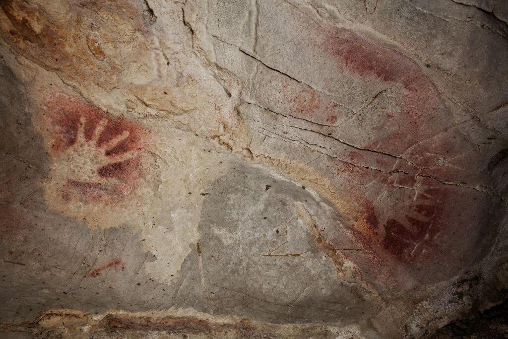 Manos pintadas en el interior de la cueva El Castillo, Puente Viesgo, Cantabria